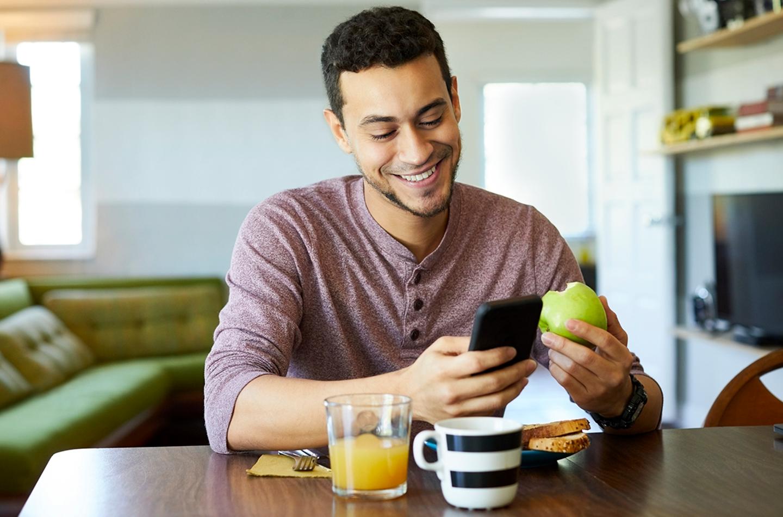 Man eating apple looking at phone
